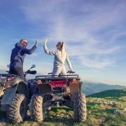 couple on 4 wheelers doing a high five